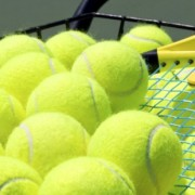 Close up of tennis balls in a basket with a raquet.